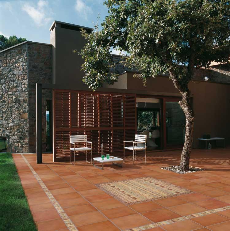 Jardín con baldosas color terracota y una mesa con sillas al fondo.