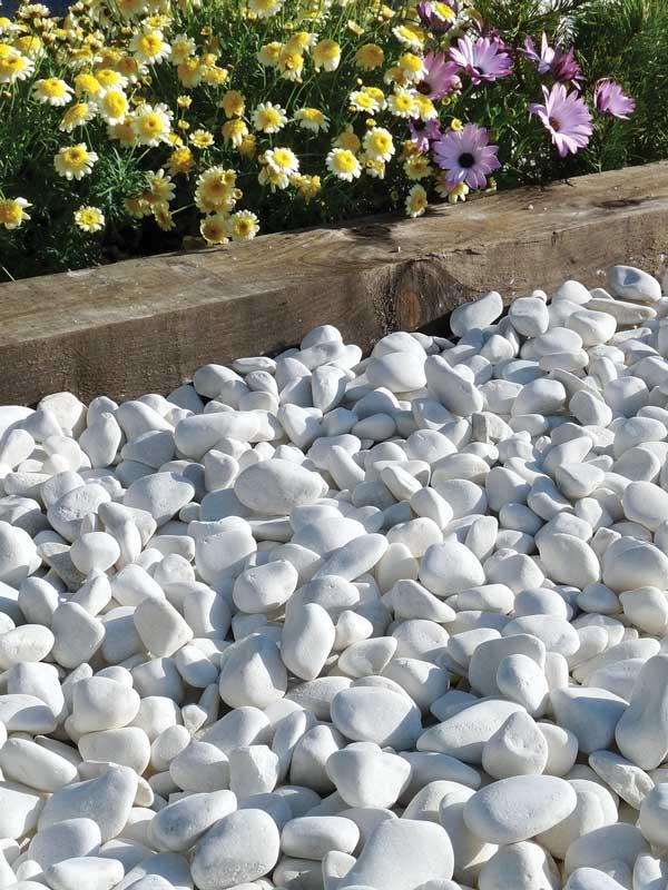 Piedra de jardín color blanco con flores en parterre de madera.