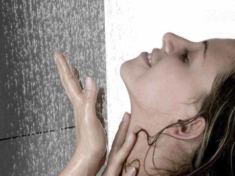 Chica debajo de la ducha con agua cayendo.