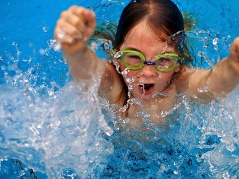 Niño con gafas de agua saliendo del agua de una piscina.