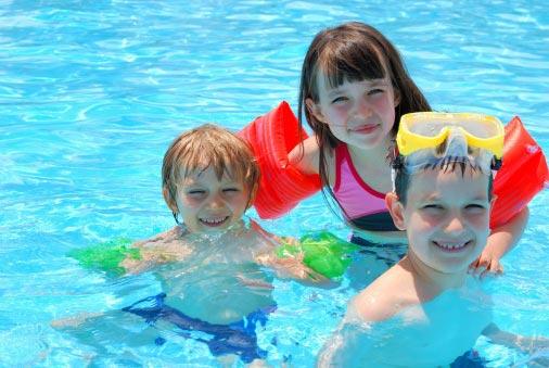 Niños con manguitos de colores y gafas de bucear en una piscina.