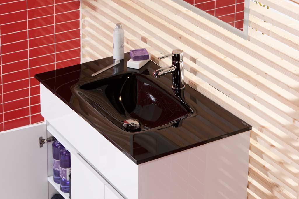 Lavabo minimalista VITRUM en vidrio negro sobre mueble de baño blanco. Toques rojo y arena.