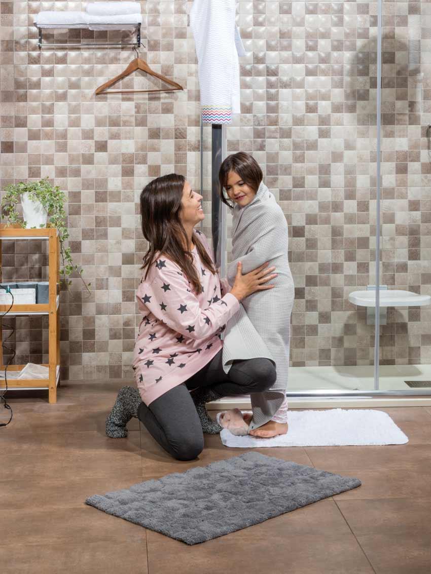 Madre en pijama secando a su hija con una toalla en una alfombra para que el baño seguro para niños.