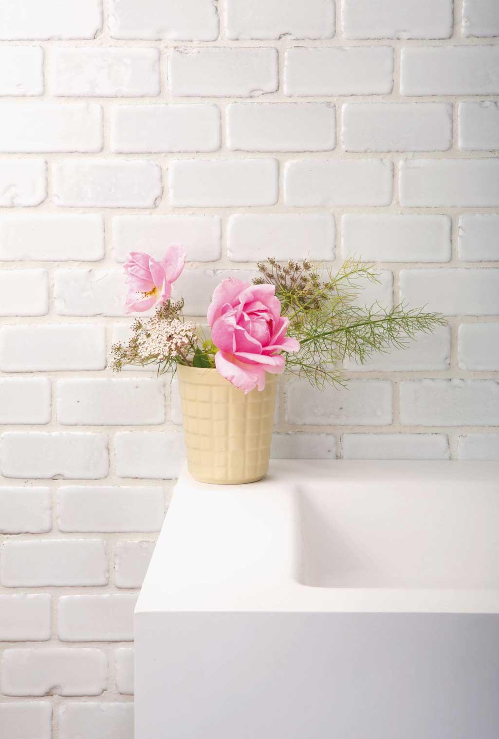 Baño de estilo nórdico con flores rosas en la repisa del lavabo. Pared de tochos pintados en blanco.