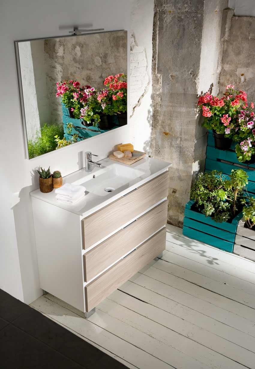 Baño de estilo nórdico con flores que aportan color y frescura. El mueble es blanco y el suelo de madera blanca.