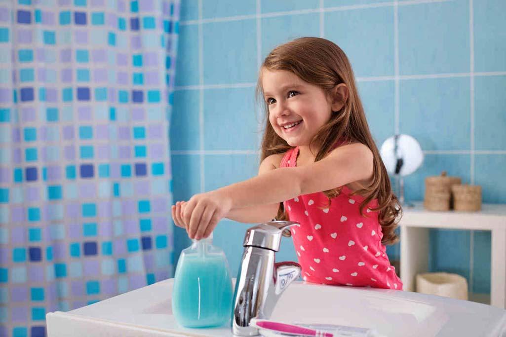 Niña vestida de rosa lavándose las manos ella sola en un baño seguro.