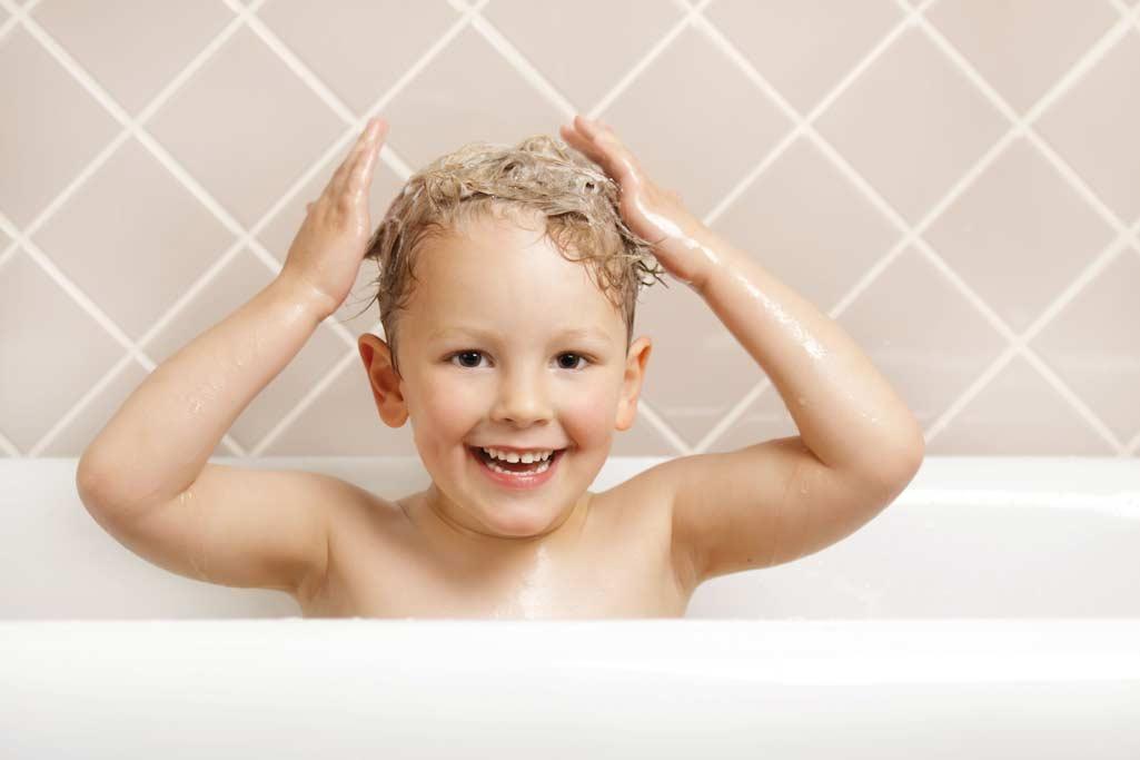 Niño en bañera haciendo la acción de lavarse el pelo en un baño seguro.