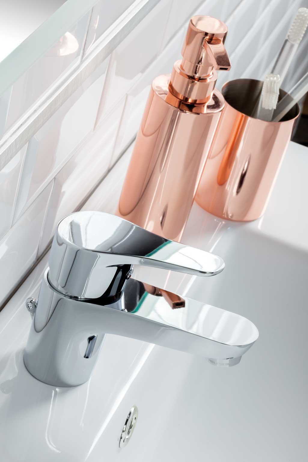Accesorios De Baño Tress:Accesorios de baño en tono cobre Están dispuestos sobre un lavabo y