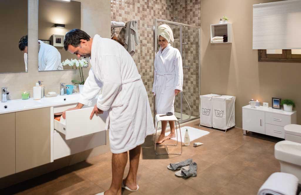 Baño en orden donde una pareja está de rutina matutina. Ella sale de la ducha y él busca algo en los cajones.