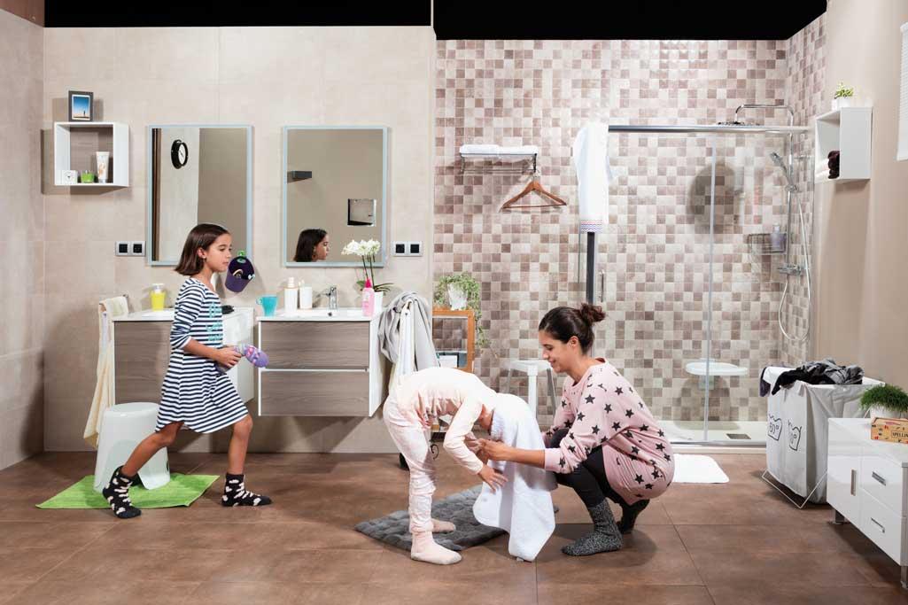 Momentos baño donde aparecen una madre y sus dos hijas. La madre está secando el pelo con una toalla a una de las niñas.