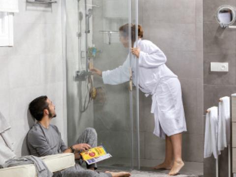 Momentos baño de una pareja donde ella está embarazada y está a punto de entrar en la ducha.