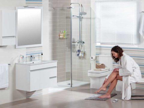 Mueble MATTY de Tattom de Grup Gamma suspendido en color blanco en un baño con una chica untándose crema en las piernas.