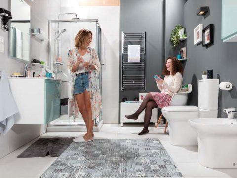 Radiador toallero en un baño con dos chicas que están riendo. Del radiador cuelga una toalla blanca.