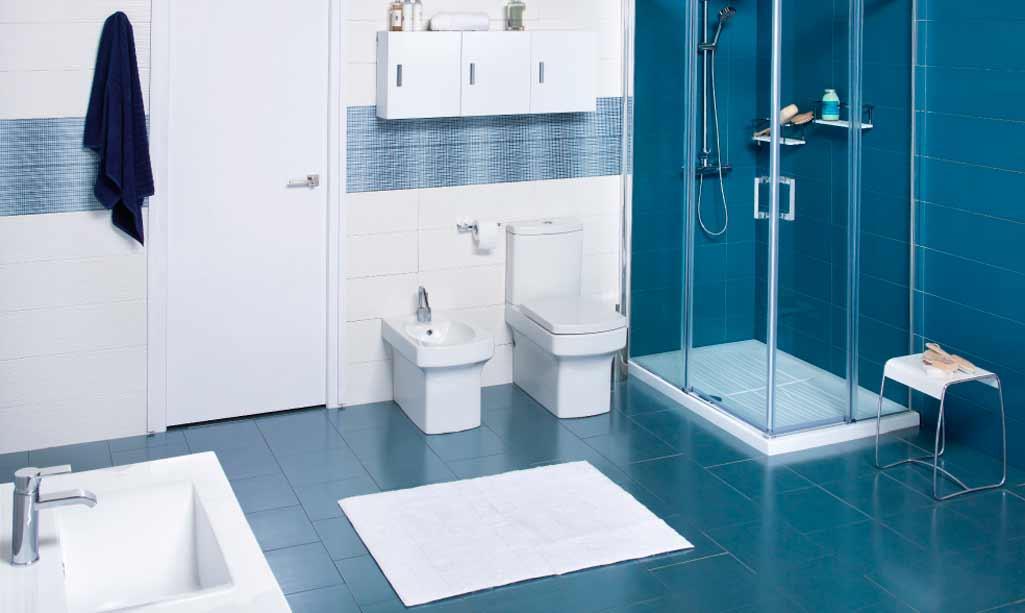 Formas rectas en el baño donde aparece un cuarto de baño completo con baldosas azules y el resto de elementos en color blanco y formas rectilíneas.