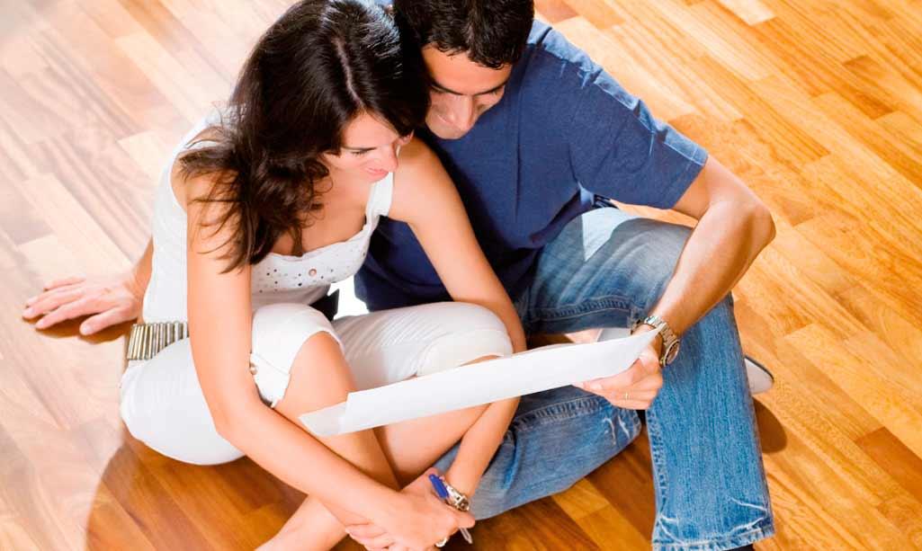 Reformar cuarto baño donde aparece una pareja sentada en el parqué de su casa mientras ojean un plano o un presupuesto.
