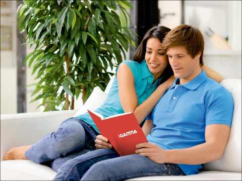 Reformar baño donde aparece una pareja sentada en un sofá ojeando un catálogo Grup Gamma.