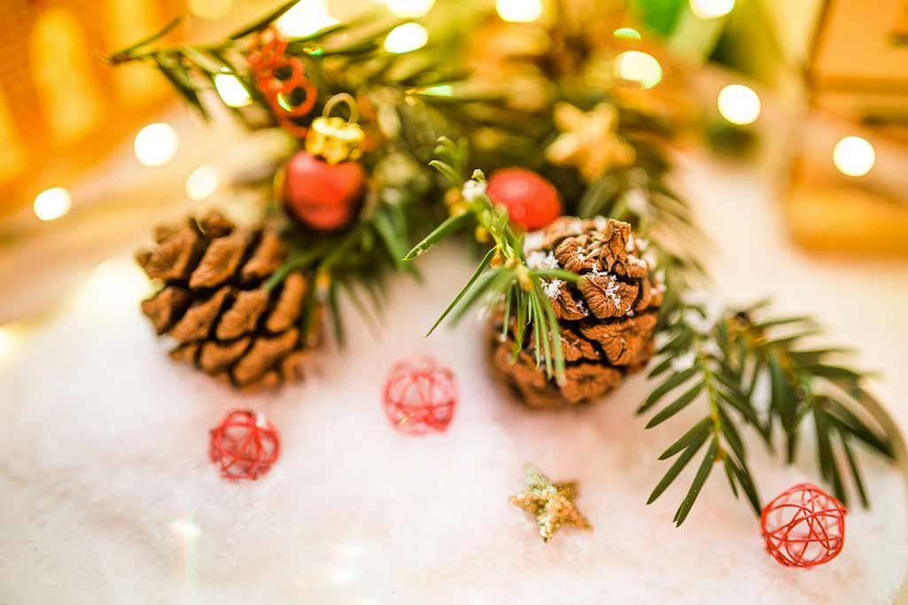 Decoración navideña con piñas y pequeñas bolas rojas y estrellas doradas.