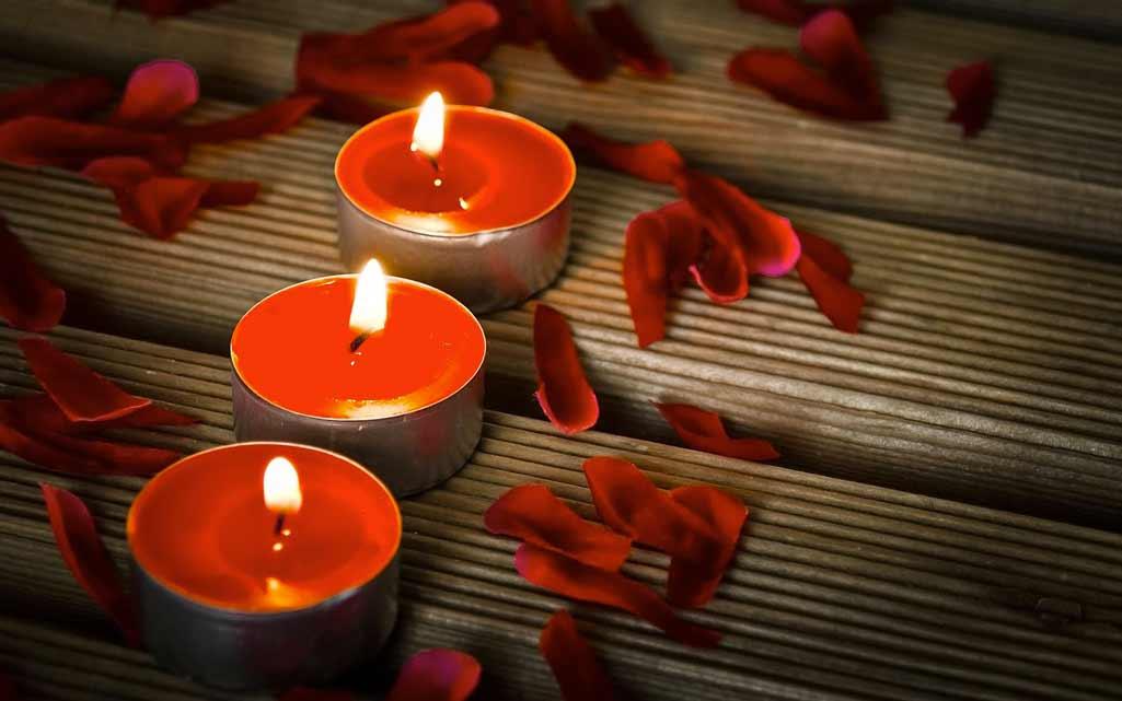 Baño navideño velas rojas redondas pequeñas en tarima de madera con pétalos de rosa también rojos.