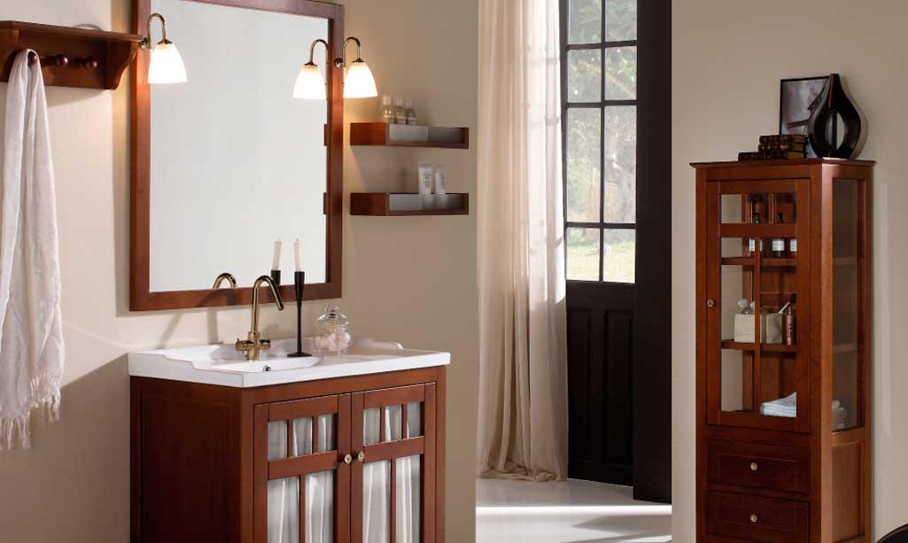 Baño de estilo vintage con paredes en colores claros y los muebles en madera algo más oscura. El mueble tiene las puertas de cristal con cortinas.