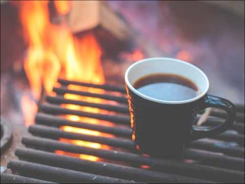 Chimeneas y estufas donde aparece una taza de café humeante apoyada en una rejilla de barbacoa. Se aprecia el fuego detrás.