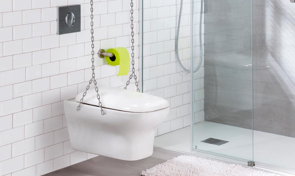 Innocent suspendido con cadenas. Es un inodoro en porcelana blanca en un cuarto de baño con baldosas blancas.