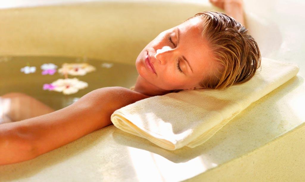 Baño bienestar donde aparece una mujer adormecida en una bañera con algunos pétalos de flores.