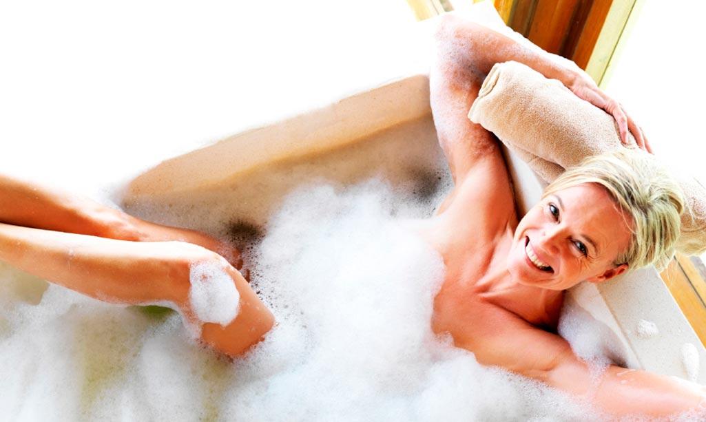 Baño bienestar donde aparece una mujer rubia feliz y sonriente en una bañera llena de espuma.