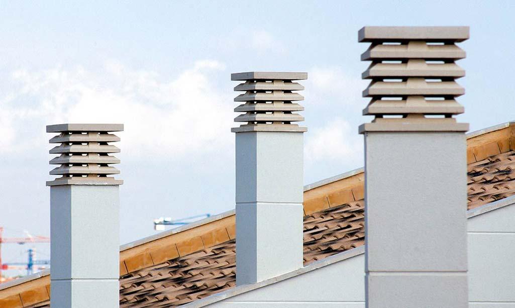 Chimenea en casa donde aparecen unos tejados con tubos de chimenea que sobresalen.