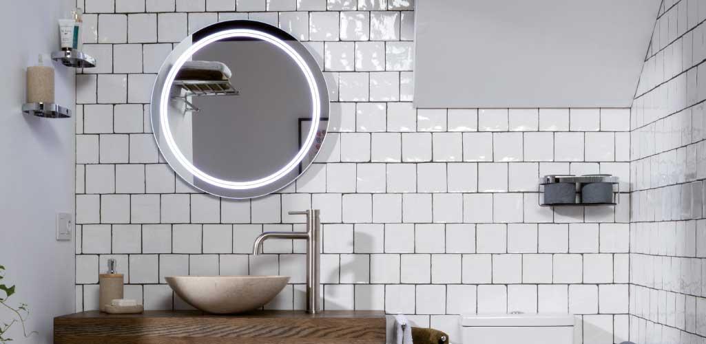 Aseos de cortesía con un espejo redondo retroiluminado en cuarto de baño con baldosas metro blancas.