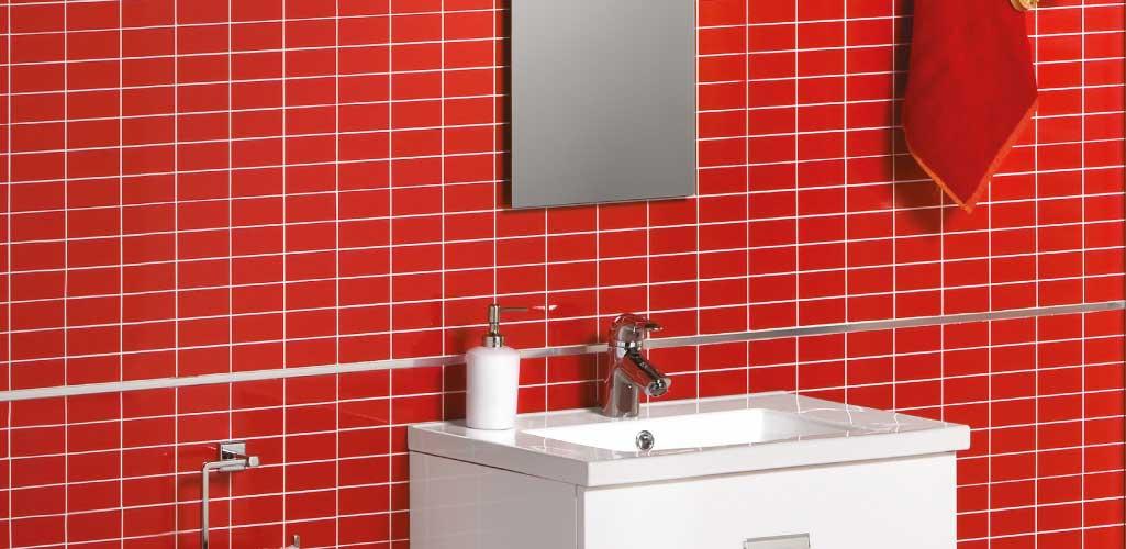 Aseos de cortesía donde puede verse un mueble de baño blanco y pequeño en un cuarto de baño con las baldosas rojas.