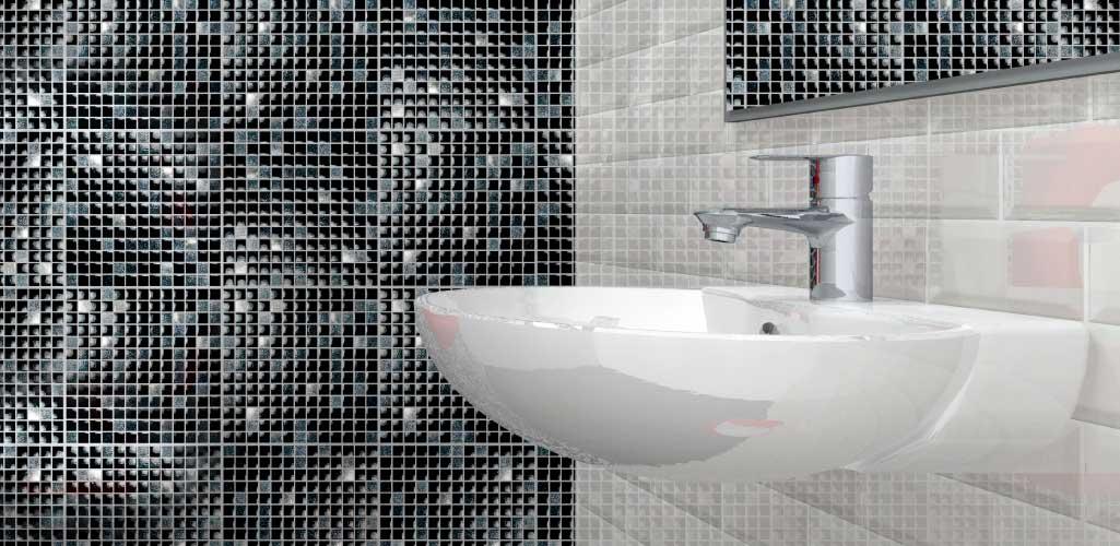 Aseos de cortesía donde la imagen es un detalle de un lavabo en cuarto de baño con baldosas negras y blancas.