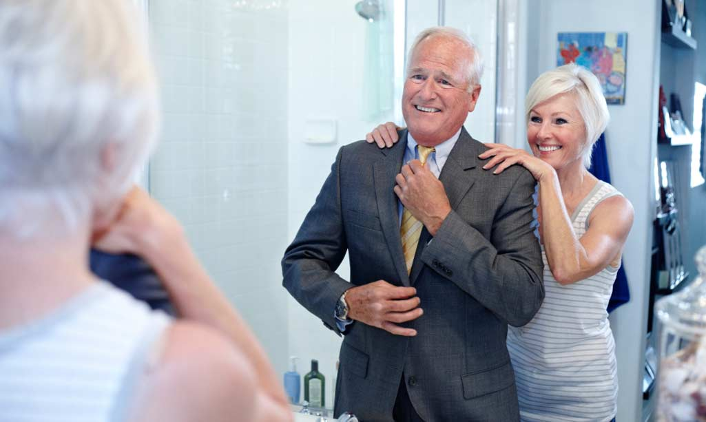 Baño gente mayor con una pareja en el baño. Él se está colocando la corbata delante del espejo y ella sonríe detrás.