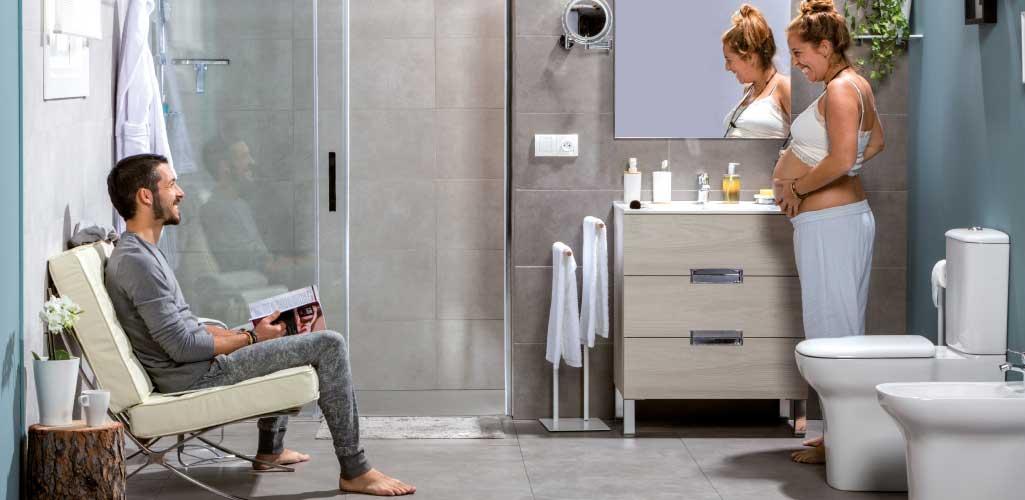 Cuarto de baño crece contigo con una pareja en la que ella está embarazada. Están en el cuarto de baño y él mira una revista.