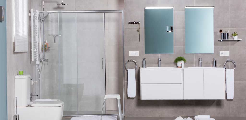 Decorar cuarto de baño con un baño completo con lavabo de doble seno y doble espejo.