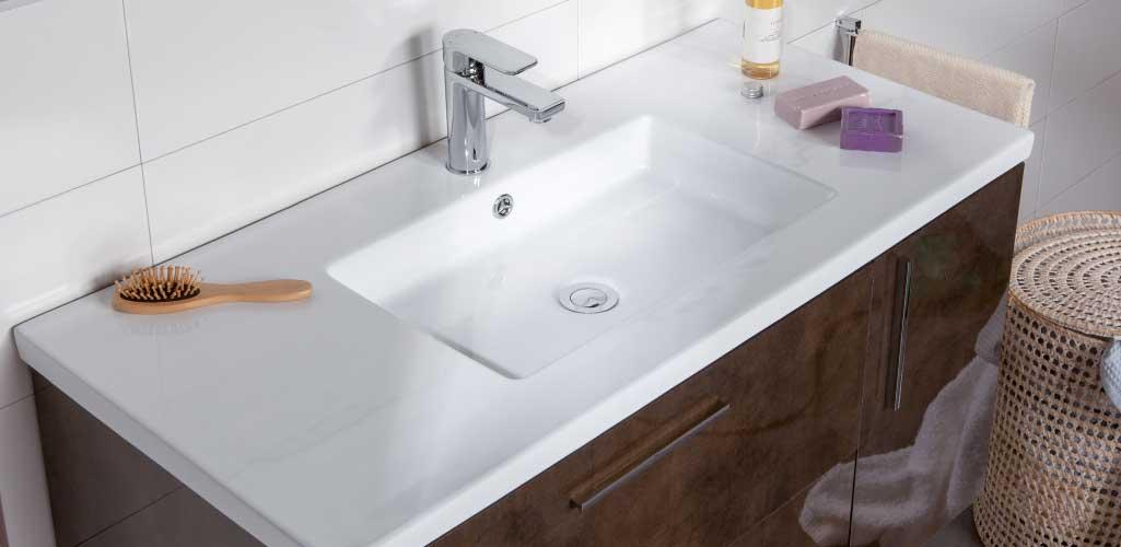 Escoger lavabo donde aparece un lavabo de porcelana blanca sobre un mueble en tono chocolate.