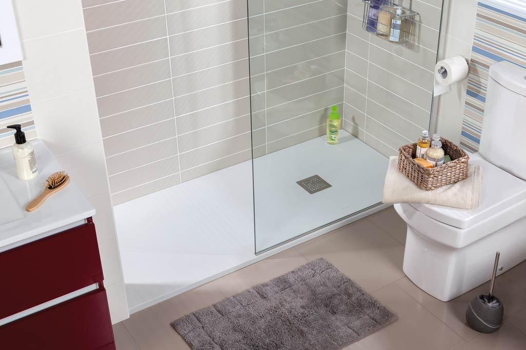 Plato de ducha GRIP en baño con azulejos grises y bote de jabón verde.