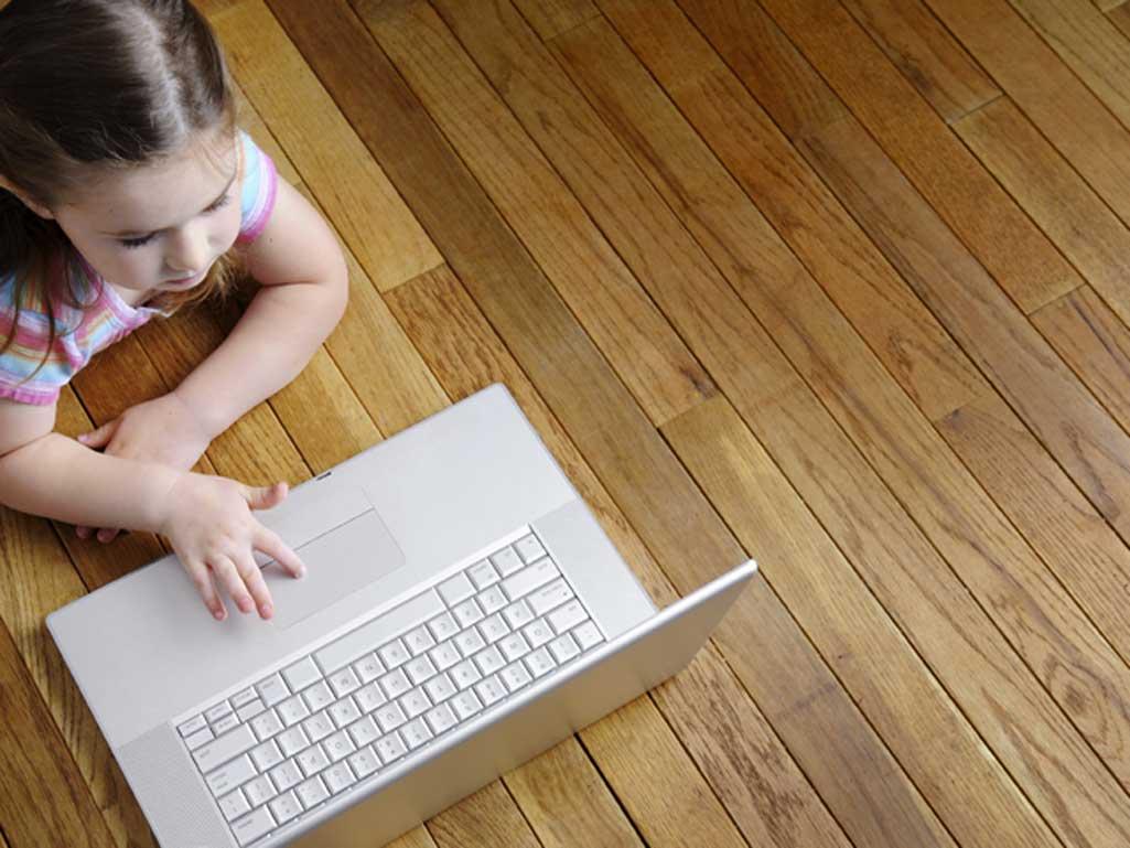 Suelo radiante con niña mirando un ordenador portátil.