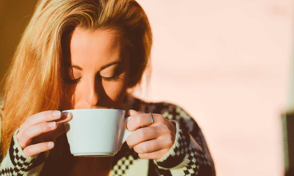 Radiadores frío en la imagen aparece una chica con jersey de lana que se está tomando una taza de chocolate.