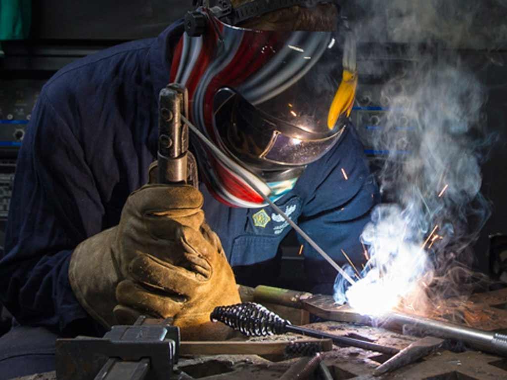 Guantes protección laboral donde aparece un hombre trabajando en una soldadura.