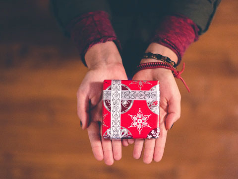 Regalo baño donde aparecen unas manos que sostienen un pequeño paquete de regalo envuelto en papel rojo y plateado.