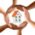 Elegir aislante para casa donde aparecen unas manos protegiendo una casa.
