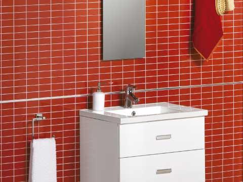 Aseos de cortesía donde aparece un mueble blanco y pequeño en un cuarto de baño con baldosas rojas.