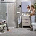 Cuarto de baño que crece contigo donde aparece una pareja. Ella está embarazada y él mira una revista.