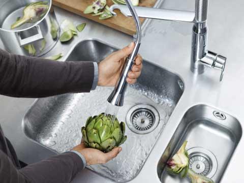 Novedades en fregaderos de cocina donde se ve las manos de un hombre limpiando alcachofas en un fregadero.